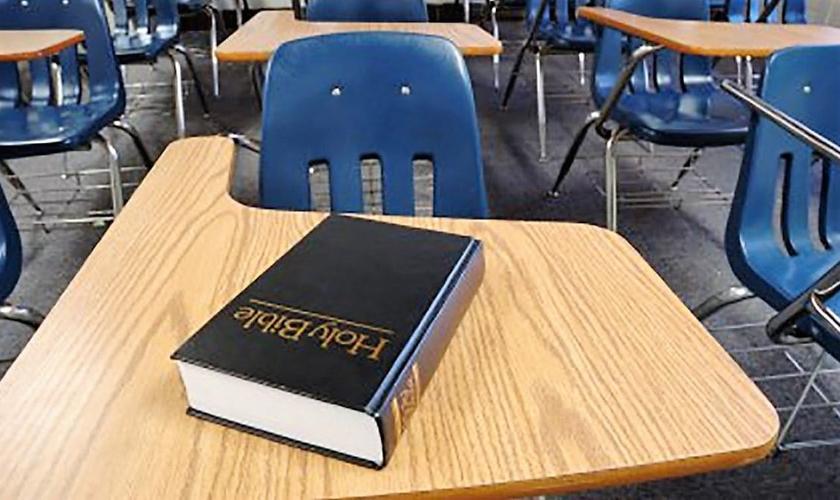 Bíblia colocada sobre carteira escolar. (Foto: The Resurgent)