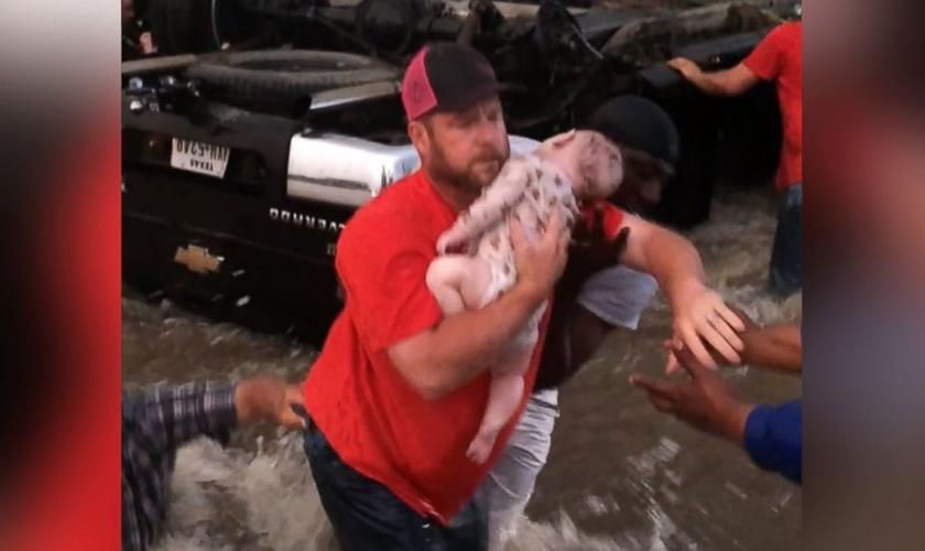 Homem retira o bebê desacordado do carro que estava preso na correnteza. (Foto: Reprodução/Facebook)