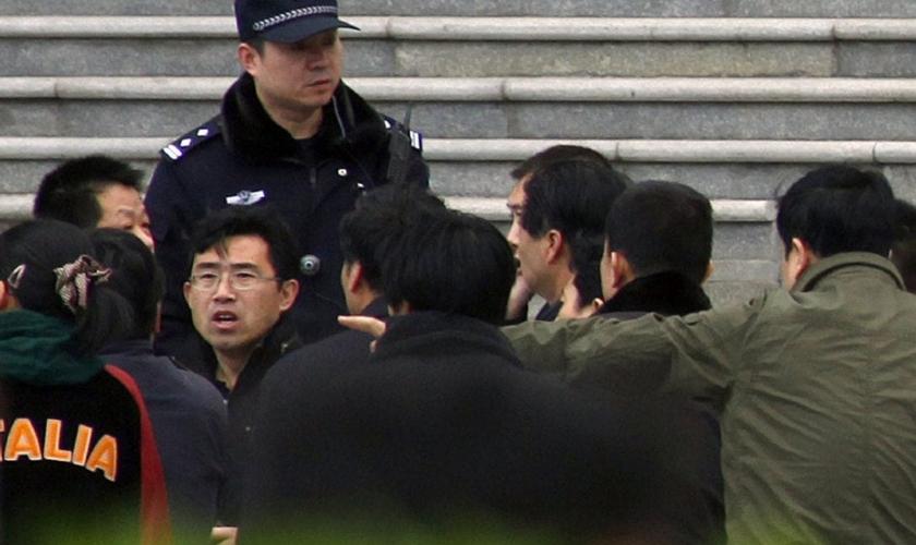 Policiais à paisana cercam um homem que estava dentro de uma igreja, em Pequim. (Foto: David Gray/Reuters)