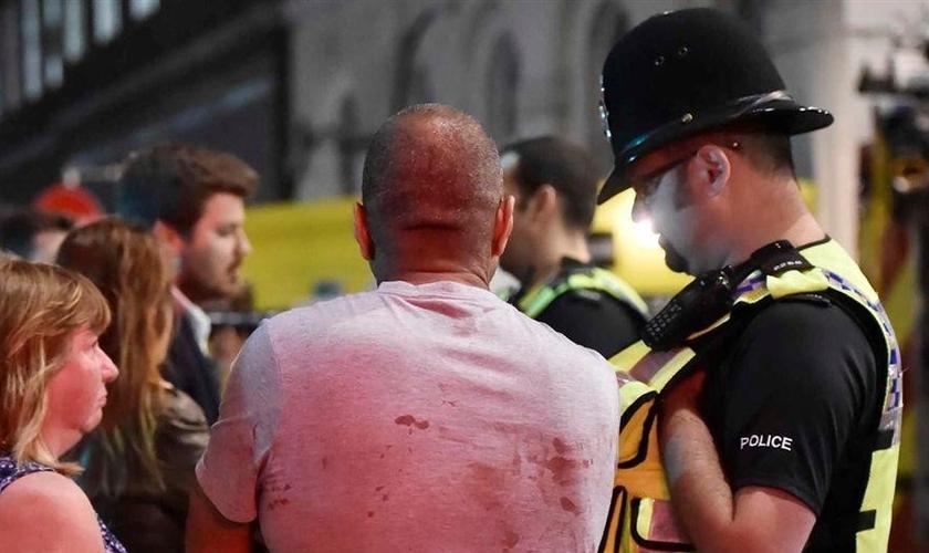 Feridos pelo ataque são atendidos por policial em Londres. (Foto: Reuters)