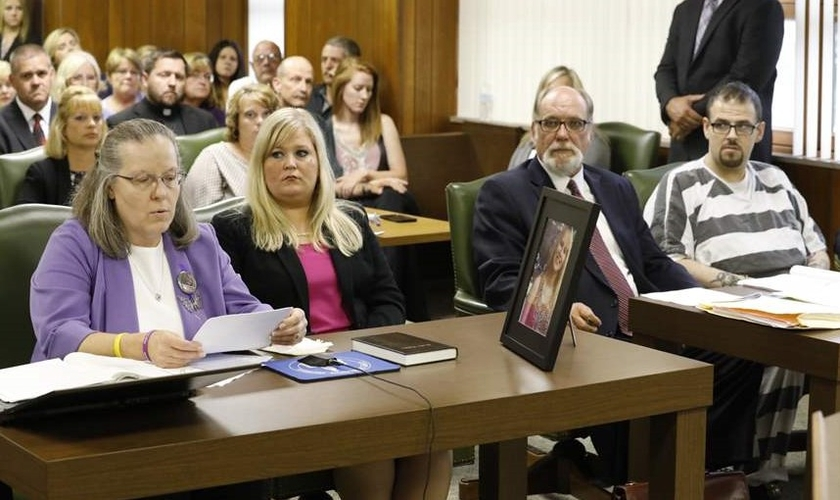 Leanda Bruck (esquerda) lê carta, enquanto repassa Bíblia a Clay Daniel (à direita). (Foto: Toledo Blade)