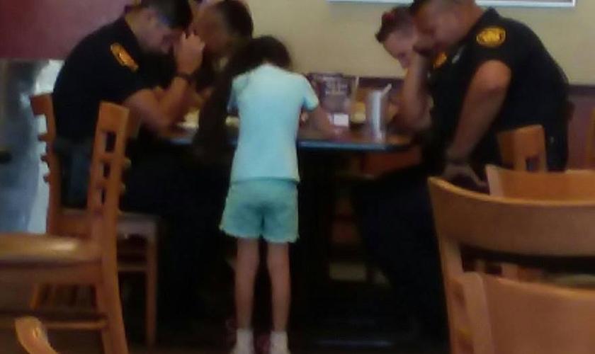 Menina de 8 anos ora por policiais que tiveram companheiro assassinado. (Foto: Reprodução/Facebook)