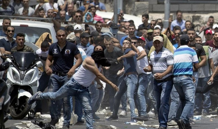 Manifestante palestino joga pedra contra as forças de segurança israelenses. (Foto: Jack Guez/AFP)