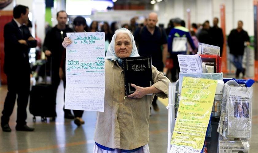 Sem ouvir desde os 38 anos, Dona Isaura carrega a Bíblia e cartazes. (Foto: Rafaela Felicciano/Metrópoles)