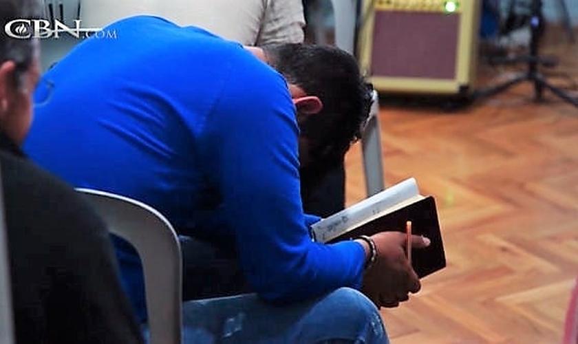 Jovem cristão iraniano ora em estudo bíblico. (Imagem: CBN.com)