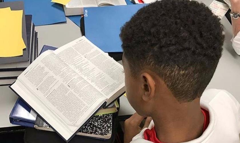 Garoto lendo a Bíblia. (Foto: Bible in The Schools)