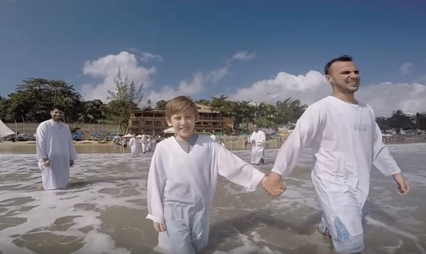 Caê se batizou em setembro de 2016 ao lado do padrasto. (Foto: Reprodução/YouTube)