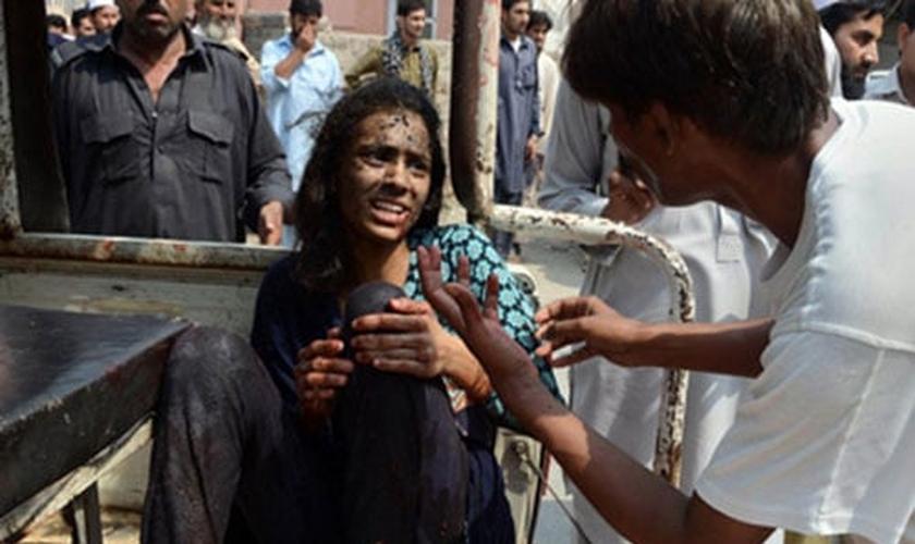 Kashmala Munawar segura sua perna, após ser socorrida próximo à igreja bombardeada no Paquistão. (Foto: British Pakistani Christian Association)