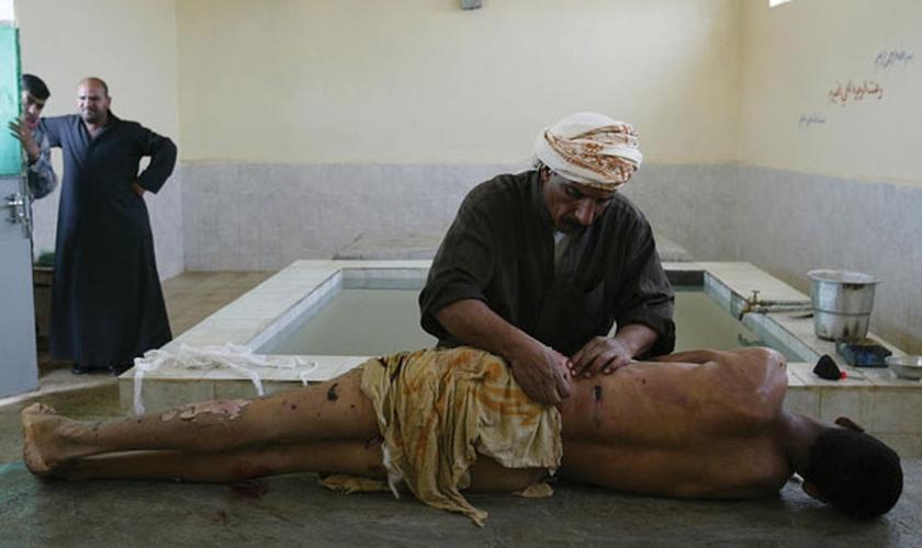 Imagem ilustrativa. Homem preparando o corpo para um enterro muçulmano em Najaf, no Iraque. (Foto: João Silva/The New York Times)