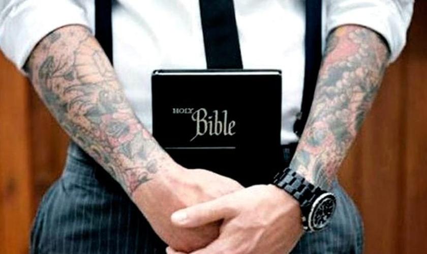 Braços tatuados seguram Bíblia. (Foto: cinconoticias.com)