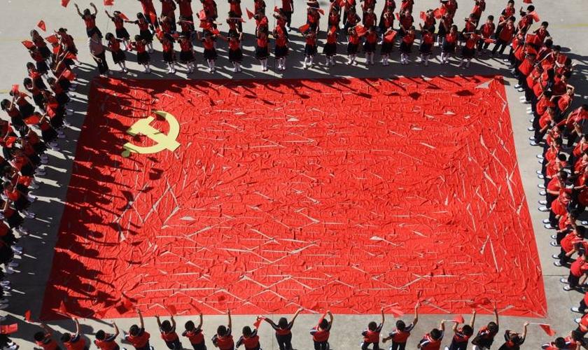 Estudantes ao redor de uma bandeira do Partido Comunista Chinês, na província de Shandong. (Foto: Reuters)