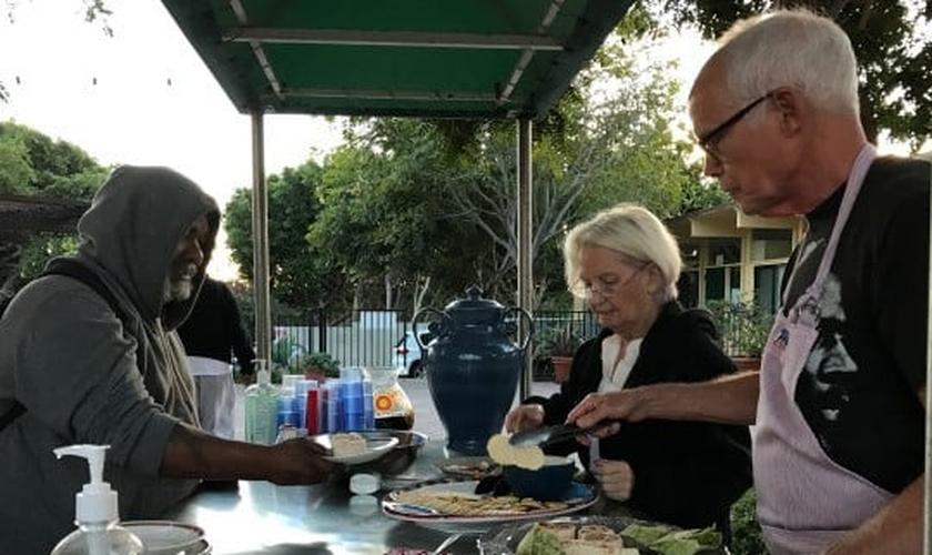 Morador de rua recebe refeição em espaço organizado pela Igreja Metodista Unida, em Malibu. (Foto: Orange County Register)