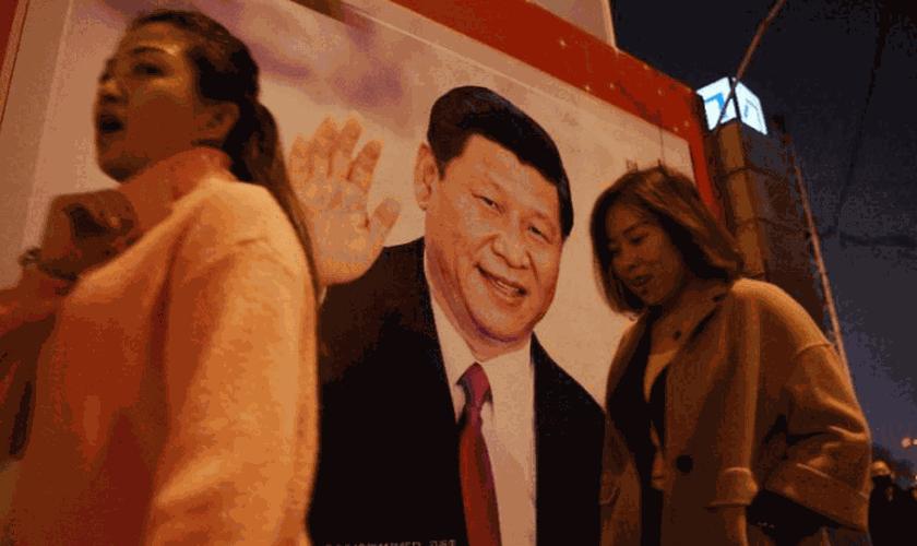 Pessoas passam por foto do presidente Xi-Jinping, exposta em rua da China. (Foto: Breitbart)