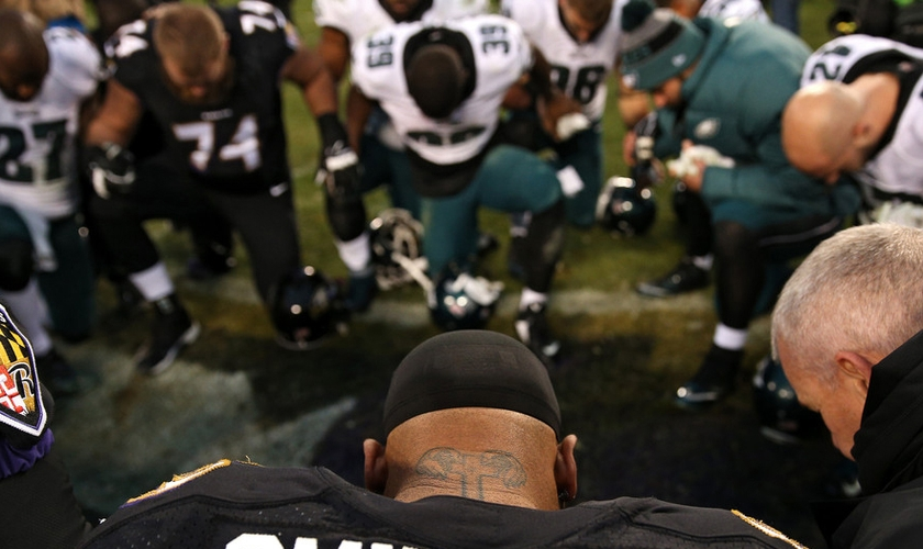 Steve Smith orando com jogadores da Philadelphia Eagles em Baltimore, Maryland. (Foto: Patrick Smith/Getty Images)