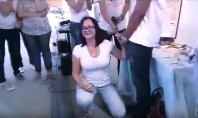 """Professora se ajoelha diante de aluno, antes de """"simular"""" um ato de sexo oral nele. (Imagem: Youtube)"""