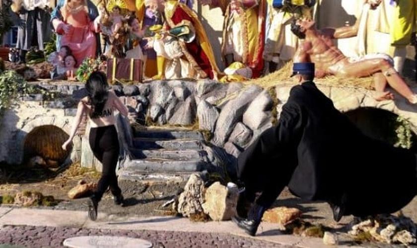 Feminista corre em direção ao presépio, enquanto é seguida por policial, no Vaticano. (Imagem: REUTERS VIDEO)