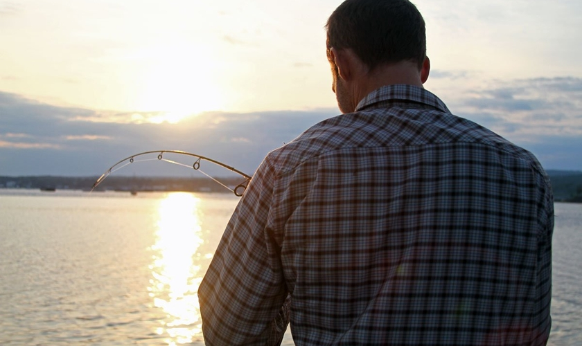 Imagem ilustrativa. Homem de costas para a câmera ajustando sua linha de pesca. (Foto: Nicko Margolies)