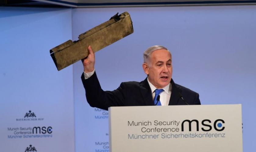 Primeiro-ministro de Israel, Benjamin Netanyahu segura pedaço de drone iraniano que invadiu território israelita por meio do espaço aéreo. (Foto:  TPS/AMOS BEN GERSHOM)