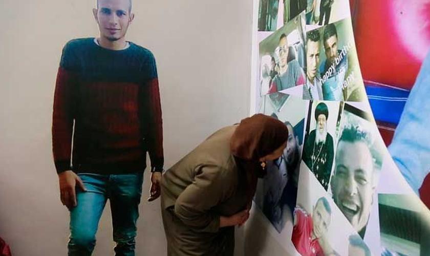 Quando tem saudades, Hanan visita uma parede cheia de fotos do filho. (Foto: Reprodução).