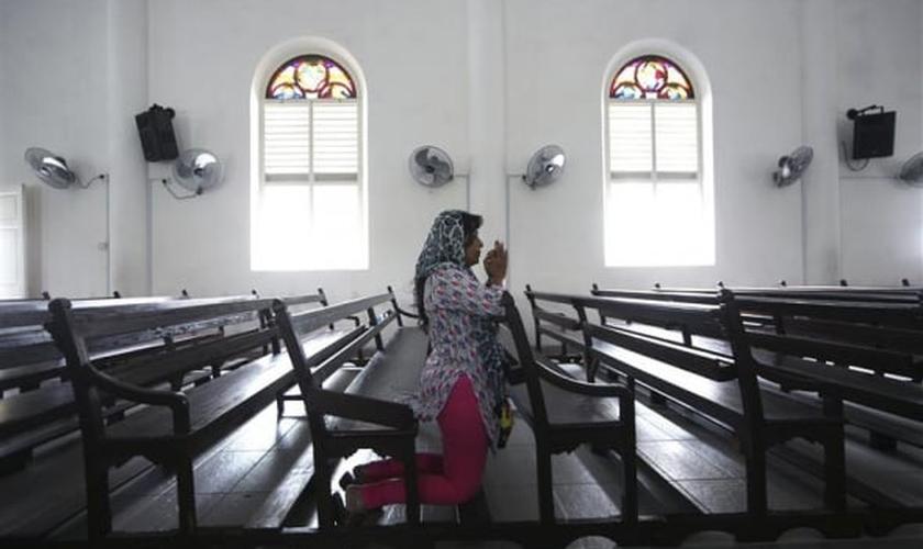 Imagem ilustrativa. Mulher orando em uma igreja na Malásia. (Foto: Reuters)