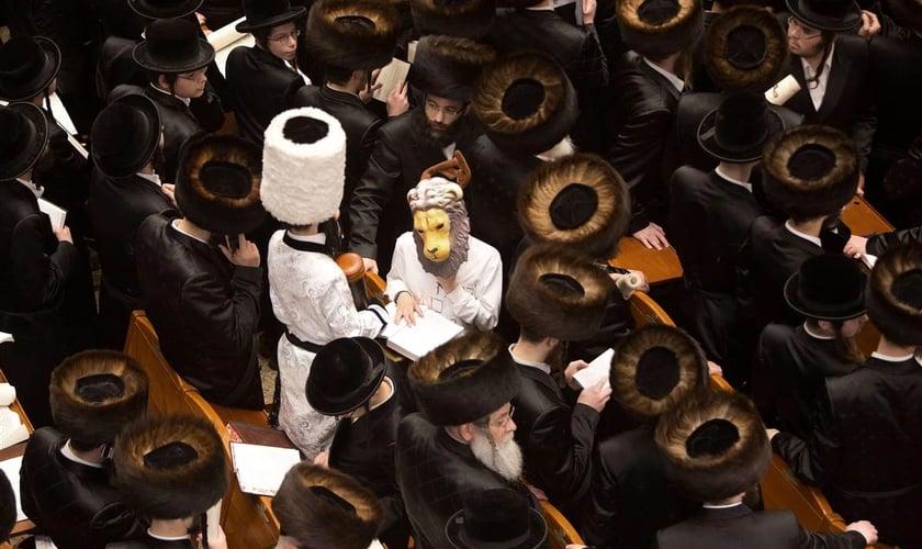Judeus lendo o livro de Ester e filhos fantasiados durante o Purim, em Jerusalém. (Foto: AFP/Getty Images)