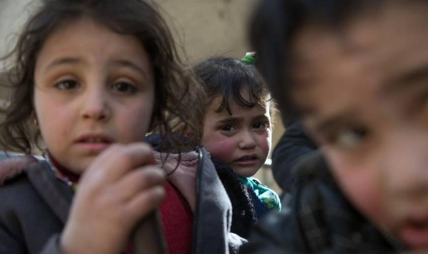 Crianças sírias fugindo de suas casas na região de Ghouta após ataques aéreos. (Foto: Abdulmonam Eassa/AFP)