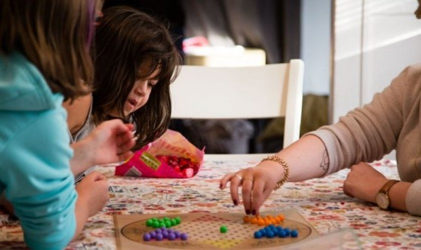 Crianças adotadas brincam em volta de uma mesa. (Foto: BECKETLAW.ORG)
