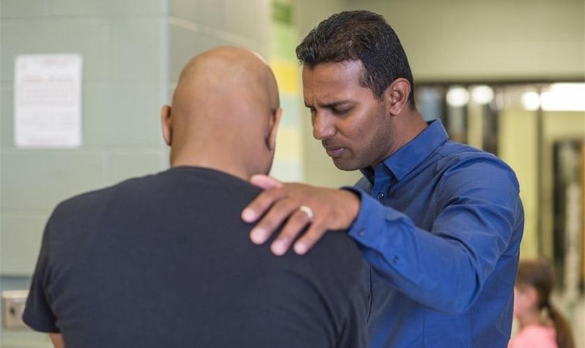 Kesavan Balasingham orando por um homem em sua igreja em Toronto, no Canadá. (Foto: NAMB)