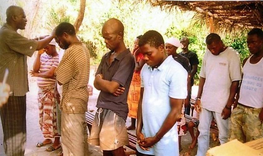 Pastor James Cuffee ora antes de batizar ex-feiticeiros na Libéria. (Foto: CHRISTIAN AID MISSION)