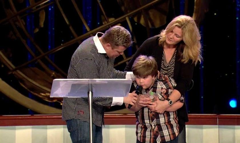 Connor recita passagem bíblica sobre cura em frente à igreja, após recuperar a fala. (Imagem: Youtube)