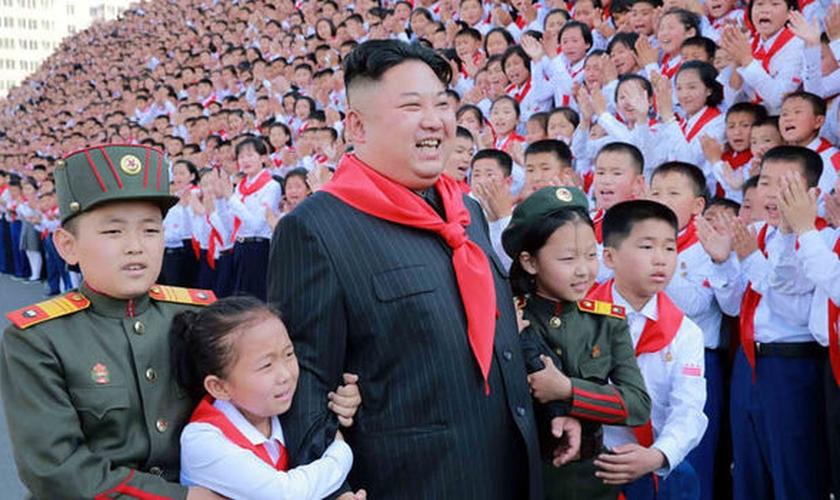 Crianças posam para foto com ditador Kim Jong Un. (Foto: Daily Express)