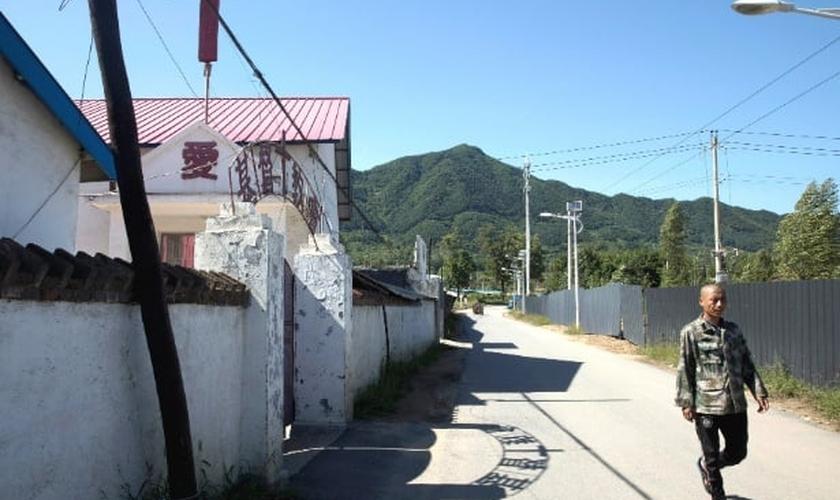 Chinês caminha em frente a uma igreja na fronteira com a Coreia do Norte. (Foto: Ng Han Guan/AP)