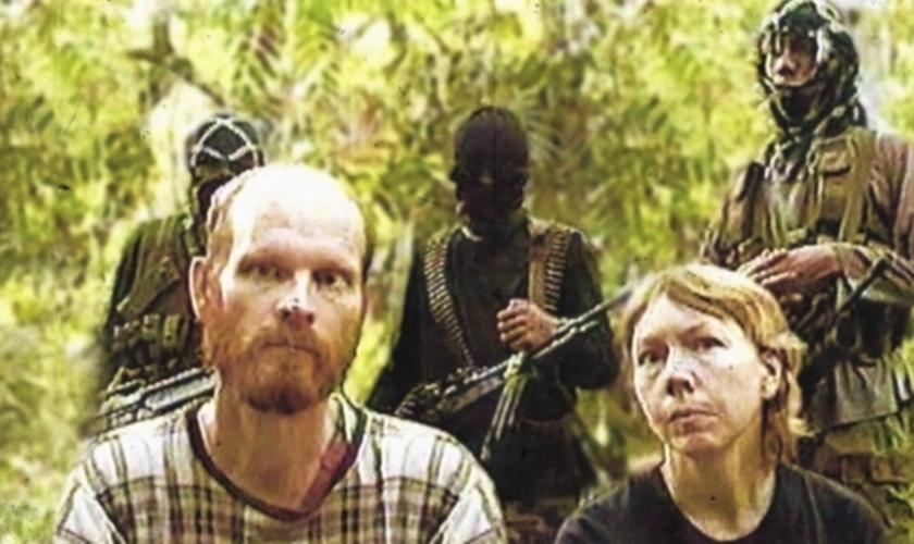 Martin (à direita) e Gracia Burnham (esquerda) com terroristas do Abu Sayaff ao fundo. (Foto: Persecution Blog)