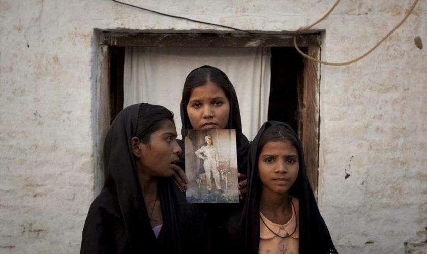 As filhas de Asia Bibi seguram uma imagem da mãe. (Foto: Reprodução).