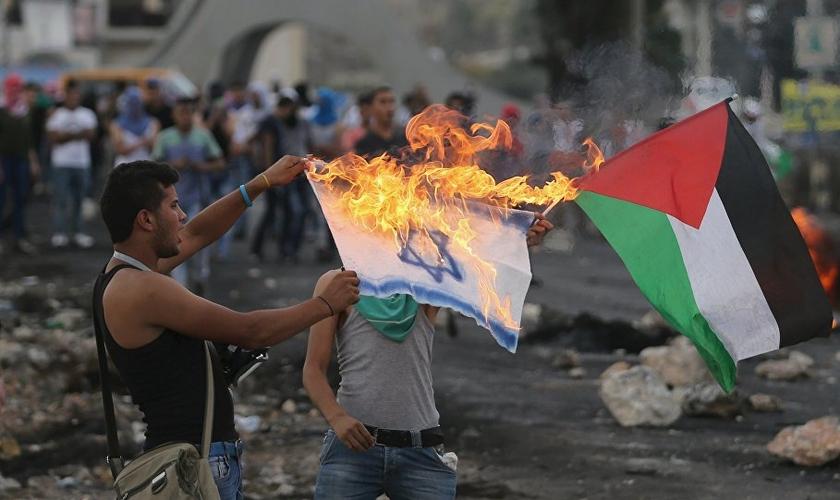 Palestino queima bandeira de Israel em protesto. (Foto: Sputnik International)