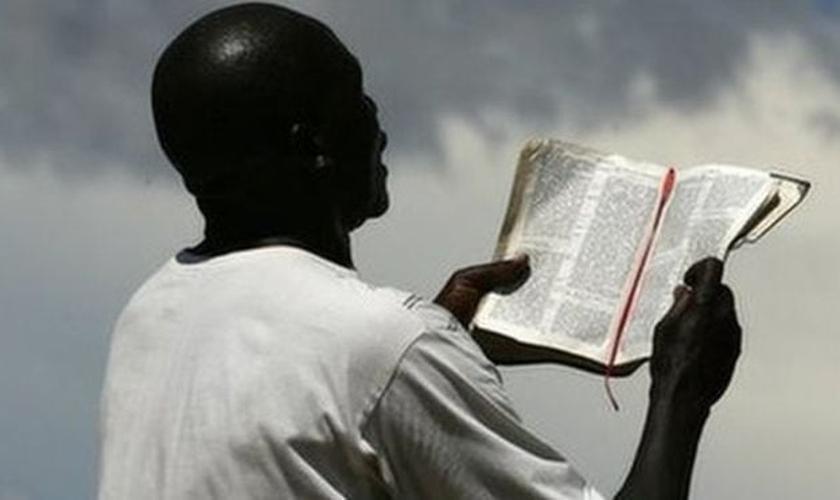 Imagem ilustrativa. Homem lendo a Bíblia Sagrada em país da África. (Foto: AFP)