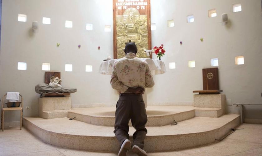 Homem ora diante de altar em igreja, em Uganda. (Foto: Reuters)