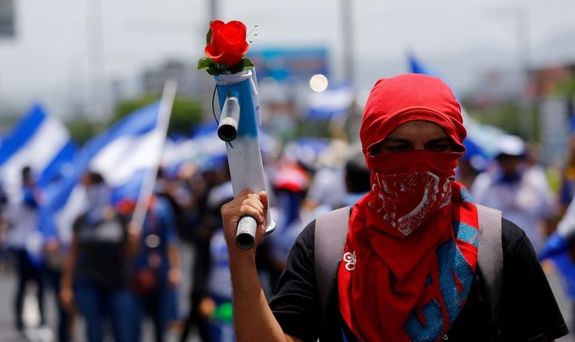 Manifestante exibe morteiro caseiro com uma flor durante marcha em Manágua, na Nicarágua. (Foto: Reuters/Oswaldo Rivas)