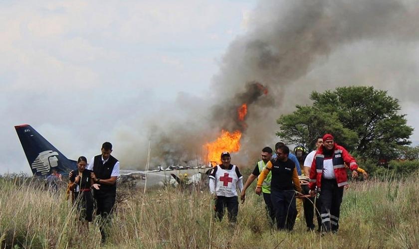 Socorristas carregam ferido em maca durante resgate após acidente com avião da Aeroméxico. (Foto: Red Cross Durango/AP)