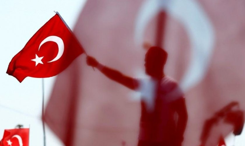 Homem segura bandeira da Turquia durante homenagem aos 'mártires da democracia'. (Foto: Reuters)