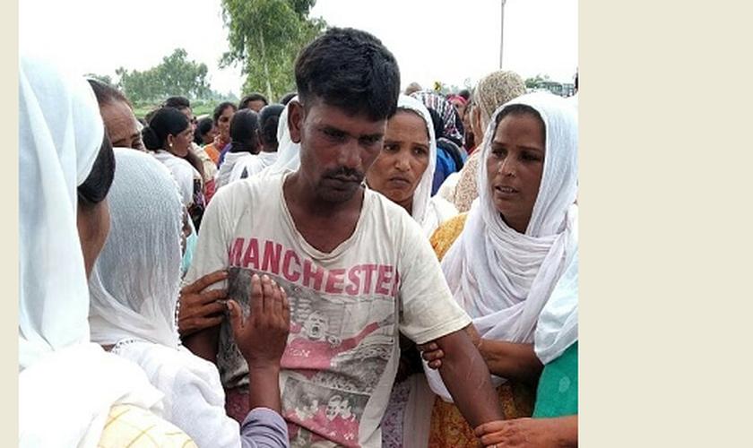 O pai de Anjali Masih sendo confortado por vizinhos. (Foto: WWM)