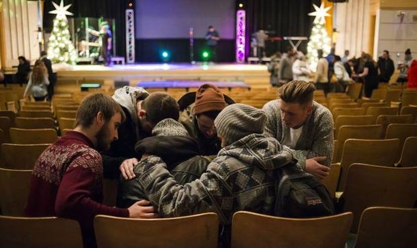 Jovens orando juntos após um culto evangélico em Toronto, no Canadá. (Foto: Christopher Katsarov/The Globe and Mail)