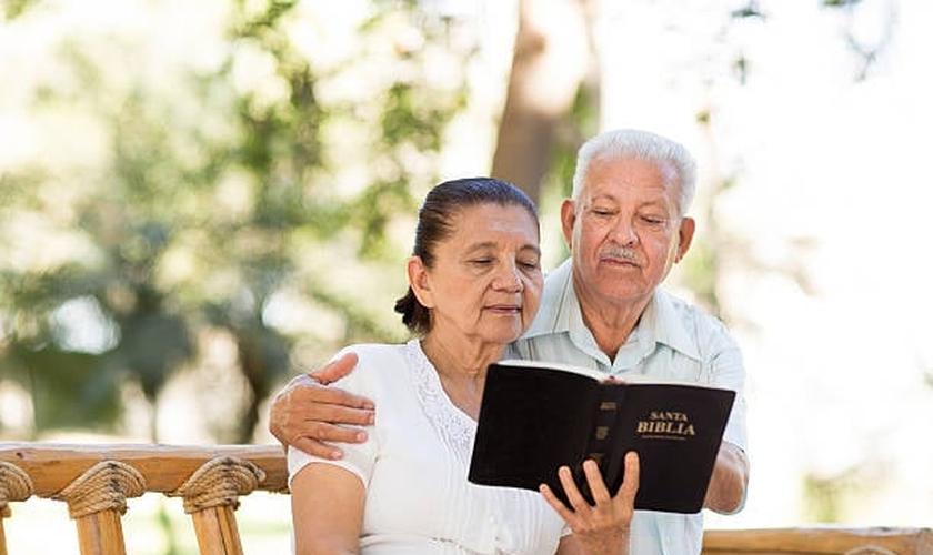 Imagem ilustrativa. Casal de idosos lendo a Bíblia Sagrada juntos. (Foto: Aldo Murillo/Captura/iStock)