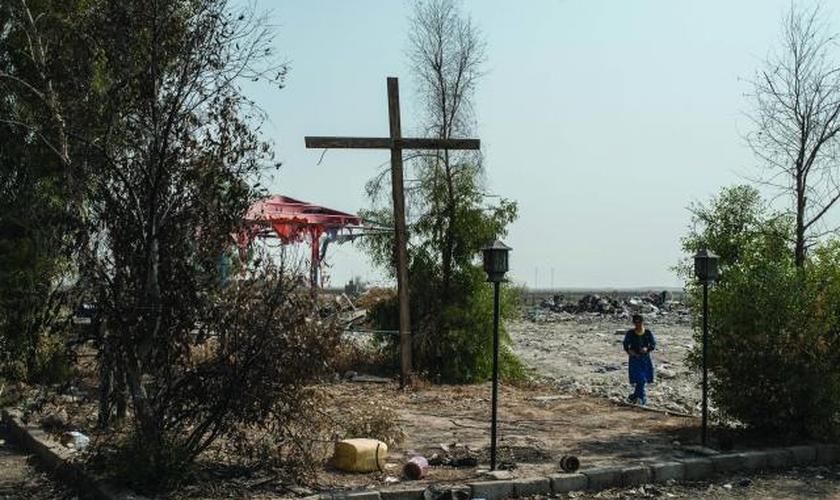Cruz erguida em uma praça da cidade de Karemlash, no Iraque, devastada por militantes do Estado Islâmico. (Foto: Martyn Aim)