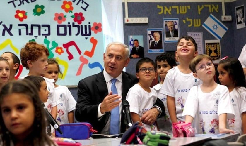 Primeiro-ministro Benjamin Netanyahu junto a crianças em escola. (Foto: Times of Israel)