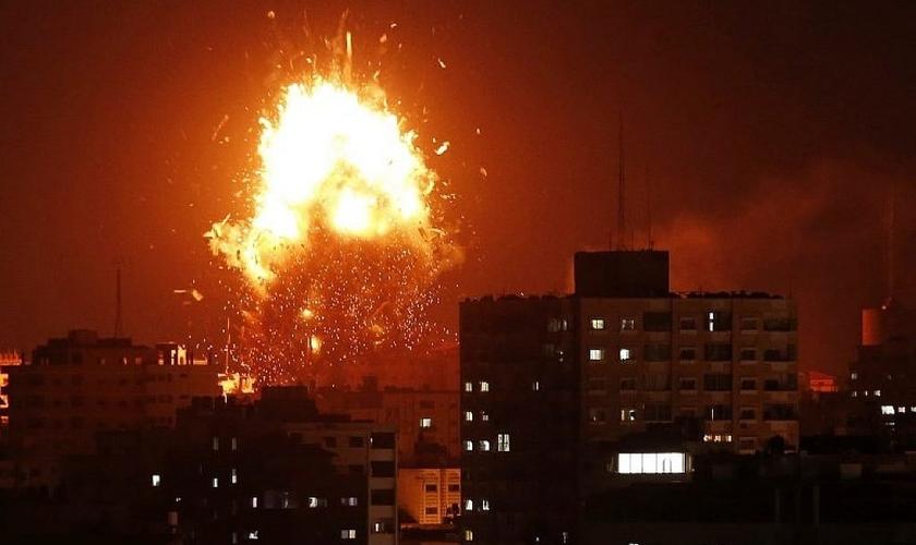 Bola de fogo sobre o prédio que abriga a TV Al-Aqsa, controlada pelo Hamas, na Faixa de Gaza. (Foto: Mahmud Hams/AFP)