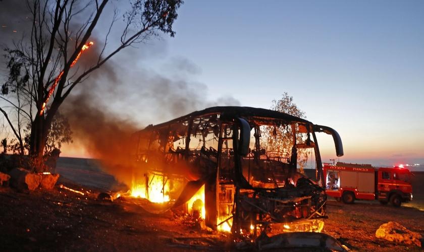 Ônibus em chamas depois de ser atingido por um foguete disparado da Faixa de Gaza, perto do kibutz de Kfar Aza. (Foto: Menahem Kahana/AFP)