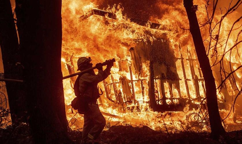 Bombeiro durante operação enquanto as chamas consomem uma casa em Magalia, na Califórnia. (Foto: Noah Berger/AP)