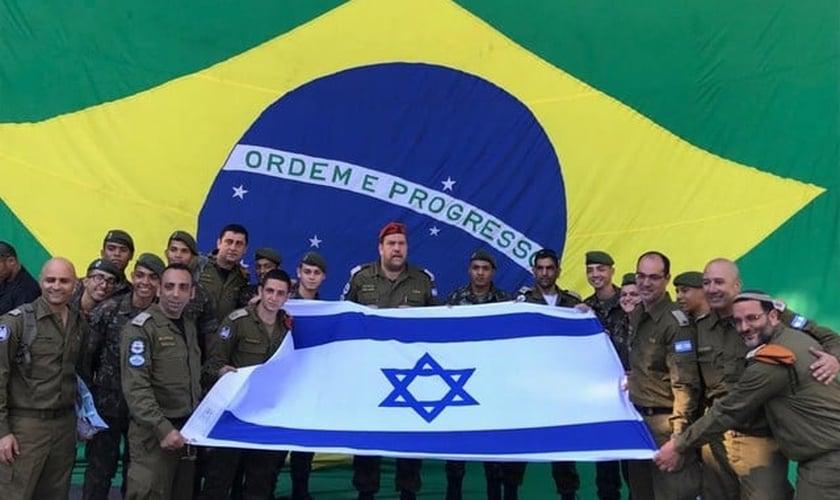Soldados posam com a bandeira de Israel, com a do Brasil ao fundo. (Foto: David Atar/Embaixada de Israel)