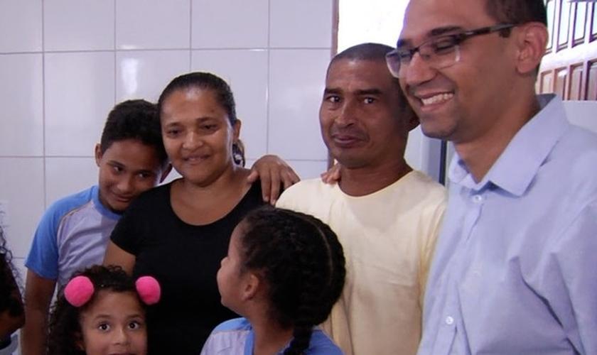 Ao lado dos filhos e do diretor da escola, casal se emocionou com nova casa. (Foto: Reprodução/TV Anhanguera)